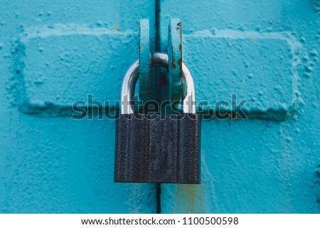Golden padlock on old blue wooden door - Shutterstock ID 1100500598
