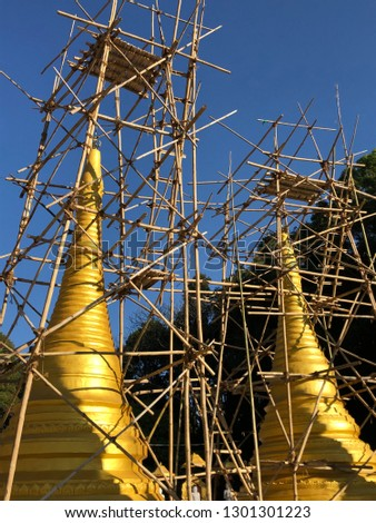 Golden pagoda, stupa, wrapped in a bamboo framework. Renovation. Myanmar, Burma
