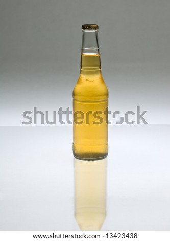 Golden pale beer in a clear bottle, back-lit, with reflection.