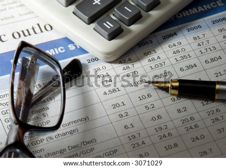golden pen, calculator and spectacles on newspaper
