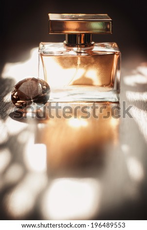 Golden Perfume Golden perfume bottle on a natural background with crystal