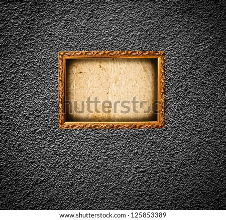 Golden photo frame on grunge wall