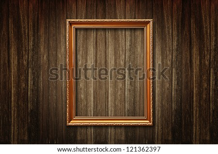 Golden picture frame on old wooden wall