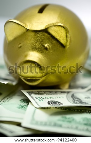 Golden piggy bank. Ceramic money box with hundred dollars banknotes.