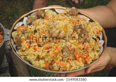 golden pilaf on a large dish in female hands. Asian cuisine Uzbek cuisine.