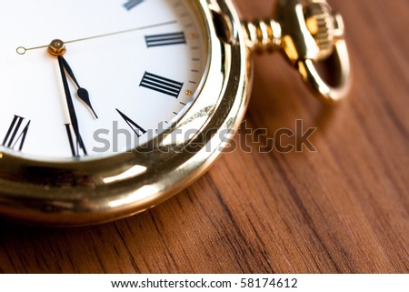 Golden pocket watch on a wooden surface (close-up)