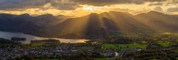 Golden rays of light breaking through clouds over Derwentwater and Keswick in the Lake District.