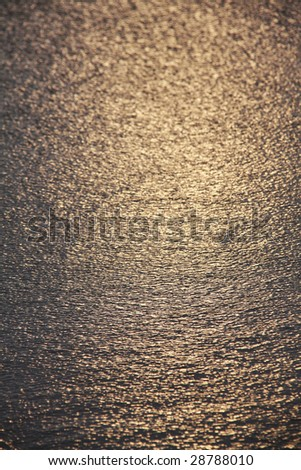 Golden reflexion of light at sunset in ocean water