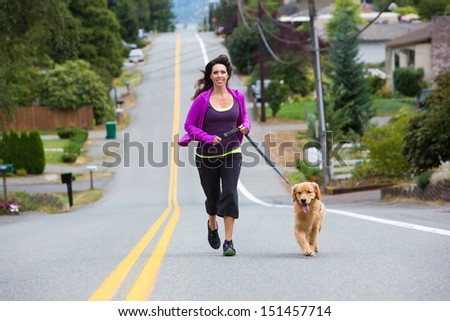 Golden Retriever dog running with a pretty woman