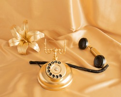 golden retro old phone and golden lilly on golden bright background. minimal abstract creative idea