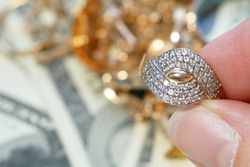 golden ring in hand, jewelry scrap of gold and silver and money, pawnshop concept, jewerly inspect and verify