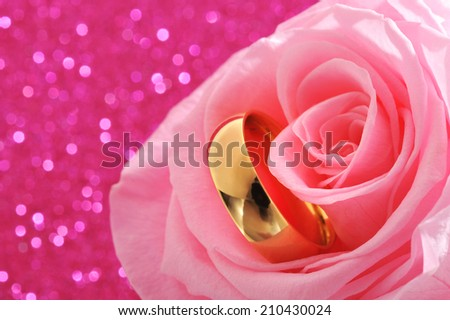 Golden ring in pink rose on pink sparkle background