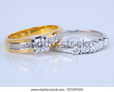Golden ring with diamond and contemporary diamond ring, isolated on white background.