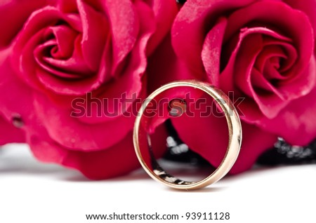 Golden ring with pearl on red flowers