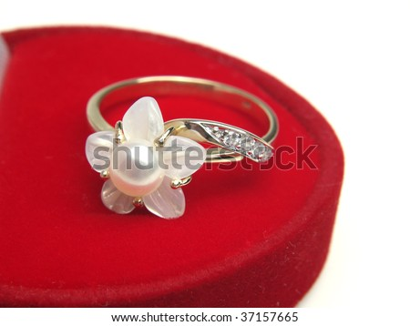 Golden ring with pearl over red box