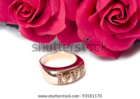 """Golden ring with word """"love"""" on it and red flowers"""