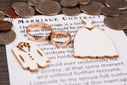 Golden rings and marriage contract. Pile of coins.