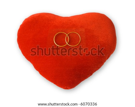 Golden rings on red heart, isolated on white