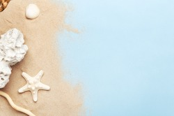 Golden sand and marine decorations. Seashell, starfish and sea stone. Copy space in right side. Isolated blue background. Summer vacation and travel concept