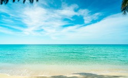 Golden sand beach by the sea with emerald green sea water and blue sky and white clouds. Summer vacation on tropical paradise beach concept. Ripple of water splash on sandy beach. Summer vibes.