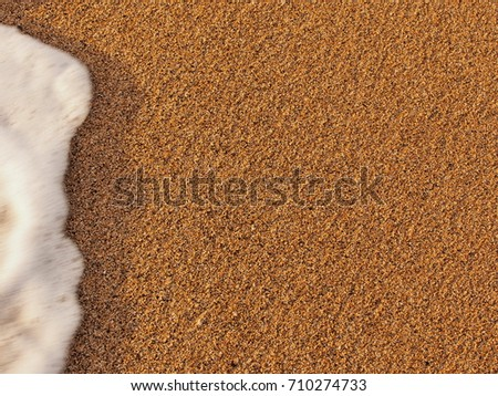 Golden sand beach with a bit of moving foam coming into the picture #710274733