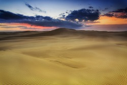 Golden sand dunes at sunrise with ranges of sand hills towards horizon with red sky near Stockon beach , NSW, AUstralia.