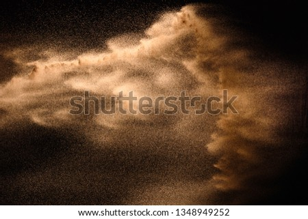 Golden sand explosion isolated on black background. Abstract sand cloud. ストックフォト ©