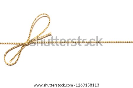 Golden satin rope parallel to frame with knotted bow gift ribbon wrap for Christmas present with intricate shine details isolated cut out top view on simple plain wide banner white background.