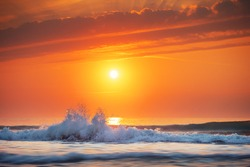 Golden sea sunrise and rolling wave on the shore