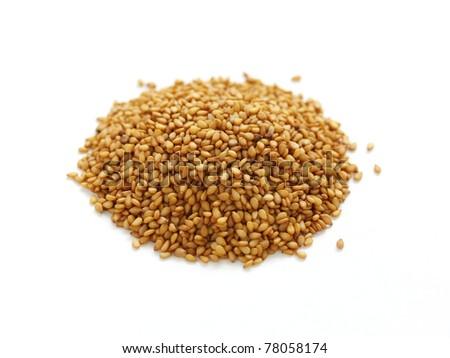golden sesame seeds piled on white background