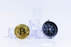 Golden Shining Bitcoin the Top of Cryptocurrency and Compass on the Ice Rock