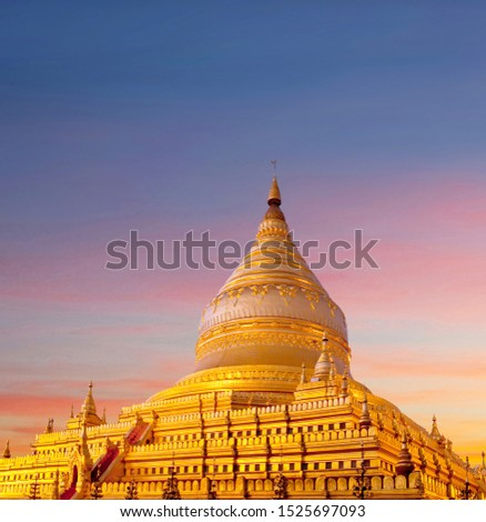Golden Shwezigon Pagoda at sunset in Bagan, Mandalay Division, Myanmar. This pagoda, a Buddhist religious place, is believed to enshrine a bone and tooth of Gautama Buddha #1525697093