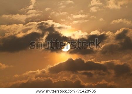 Golden sky at dusk with black clouds and The shining sun