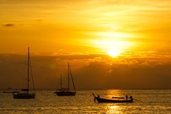 golden sky of the sunset at the sea with yacht and long tail boat