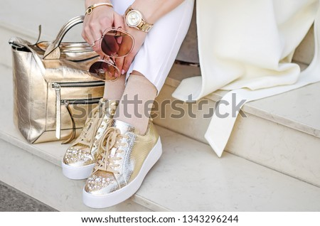 Golden sneakers, bag and watch closeup. Sunglasses closeup in female hands. The girl sits on the steps. #1343296244