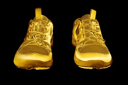 Golden sneakers black background isolated closeup, gold metal sport shoes, luxury running gumshoes, fashion yellow metallic fitness boots, athletic, football footwear, winner, victory, champion symbol