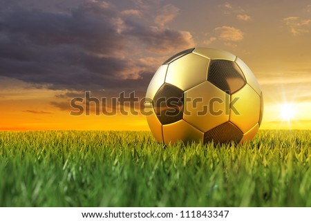 Golden Soccerball 3D on playing field under beautiful sundown