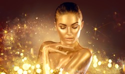 Golden sparkles skin, Woman face portrait closeup. Model girl with holiday golden Glamour shiny professional make up. Gold jewellery, jewelry, accessories. Beauty gold metallic body, fashion Xmas art.