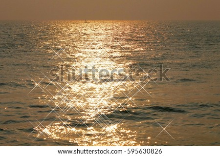 Golden sparkling on sea surface.  Morning sunlight glittering on sea with a small boat sailed faraway.  Using glistening water effect.  Sunlight reflection on waves.