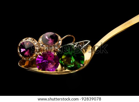 Golden spoon with jewelry such as rings with stones and rings