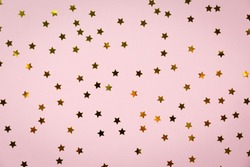 Golden star sprinkles on pink. Festive holiday background. Celebration concept. Top view, flat lay. Horizontal