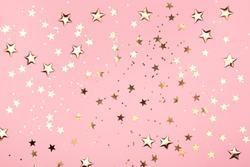 Golden stars glitter on pink background. Festive holiday pastel backdrop.