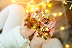 Golden stars sparkling on child's hands and palms. Christmas mood, cozy view. Bright and festive.