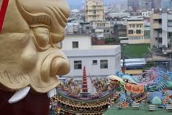 Golden statue face, typical asian fantasy style and colorful religious ornaments and oriental decoration on roof of spiritual taiwanese Mazu Hotsu Longfong Temple in Miaoli City, Zhunan, Taiwan, Asia.