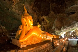 Golden statue of Buddha of Nirvana in buddhist cave temple in Wat Tham Suwankhuha cave (Monkey Cave) In Phang Nga, Thailand.
