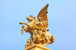 Golden statue of Pegasus held by Fame . Statue on the Pont Alexandre III in Paris