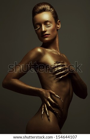 Golden statue of Valkyrie concept. Arty portrait of model with golden healthy skin and shiny lashes. Perfect sporty body. Golden long nails. Studio shot