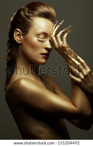 Golden statue of Valkyrie concept. Arty portrait of model with golden healthy skin and shiny lashes. Perfect sporty body. Golden long nails. Profile. Studio shot