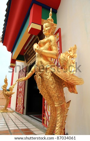 Golden statues of a Kinnari (half-bird, half-woman creatures), standing at the entrance of Anek Kuson Sala, known as Viharnra Sien in Pattaya, Thailand