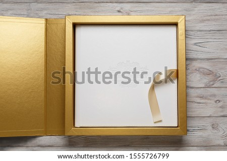 golden stylish square gift cardboard box with lid for photo album. Bright original box for wedding photo album with white leather cover. leather family photo book in the open box with lid and ribbon.. Сток-фото ©
